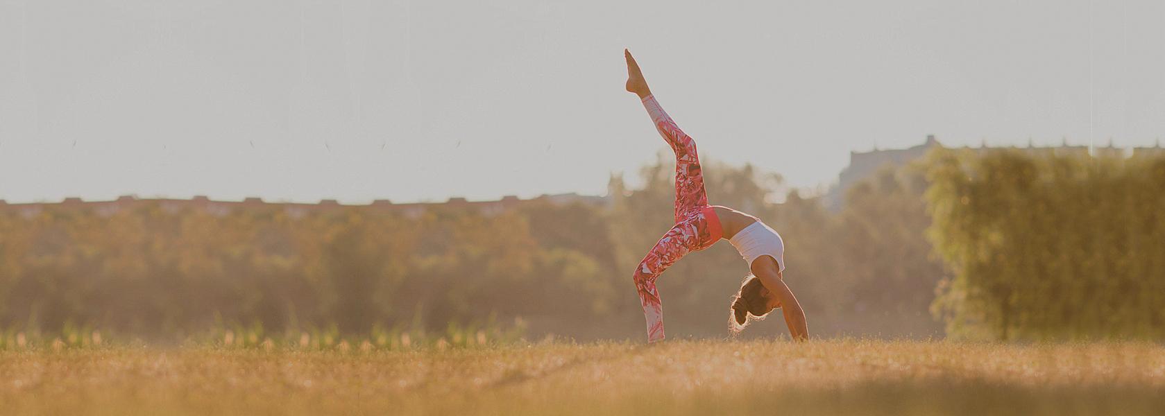Eine Dame macht eine Yogafigur im freien auf einer Wiese