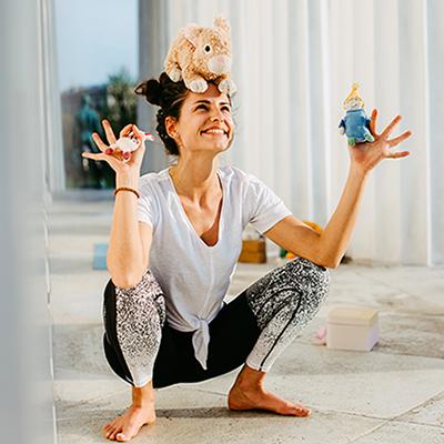 Frau mit Kinderspielsachen in der Hand und am Kopf.