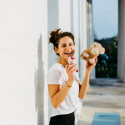 lachende junge Frau mit Kinderspielzeug in den Händen