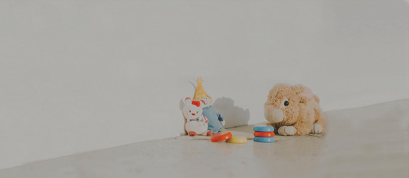 Kuscheltiere und Kinderspielzeug vor einer weißen Wand