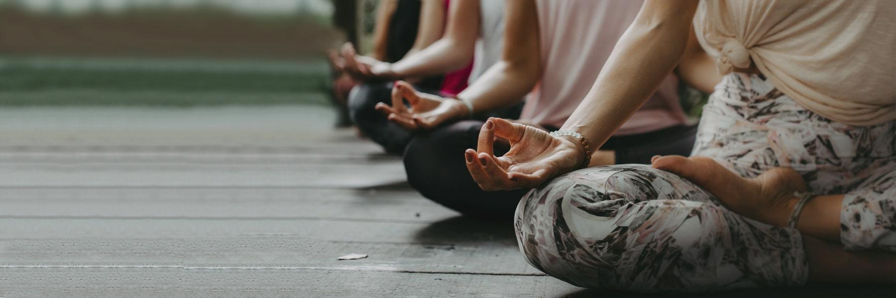 Meditierende Personen im Schneidersitz