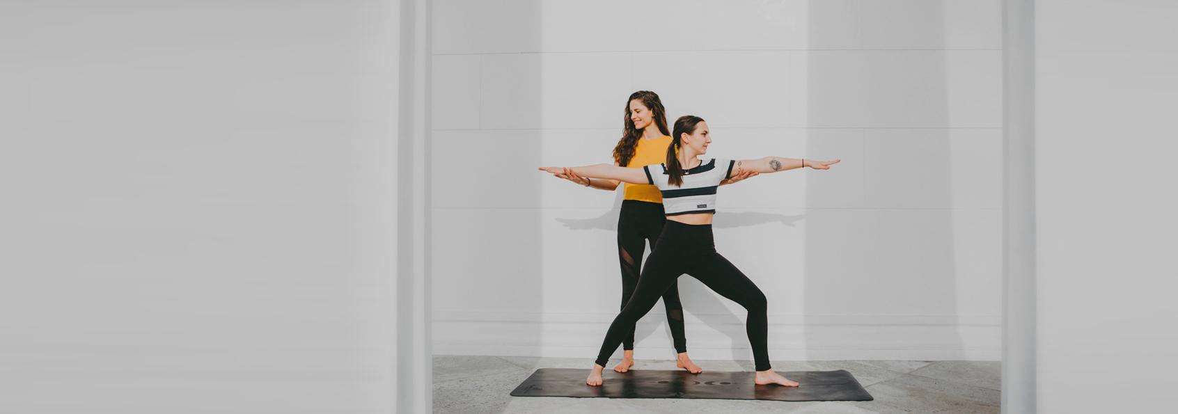 Zwei Frauen, eine in einer Yogapose.