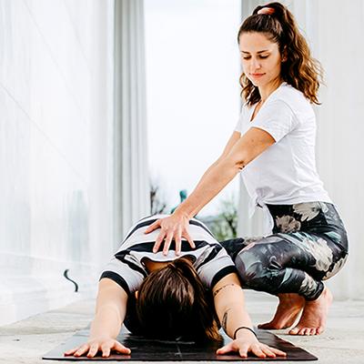 eine Frau untersützt eine andere bei einer Yogaposition