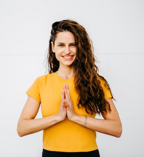 Glückliche Frau in gelbem Shirt beim meditieren