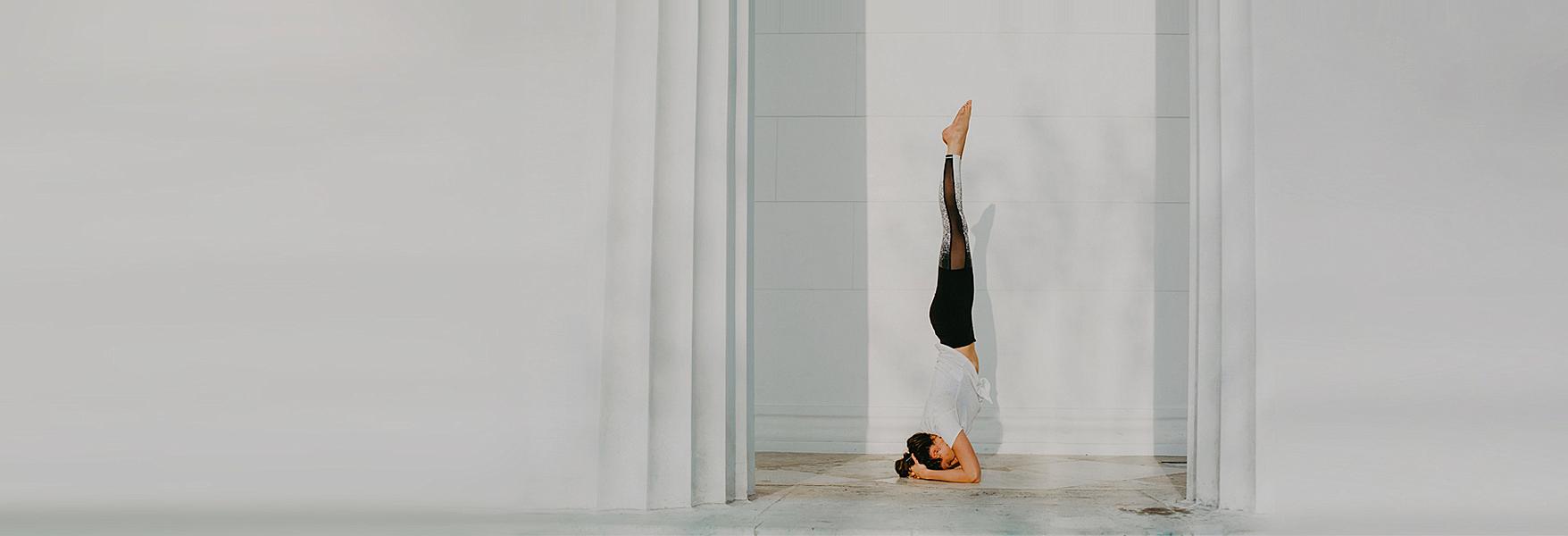 Frau vor weißem Hintergrund im Yoga Kopfstand