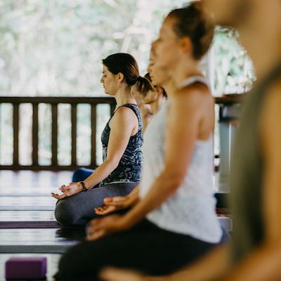 Menschen meditieren im Schneidersitz