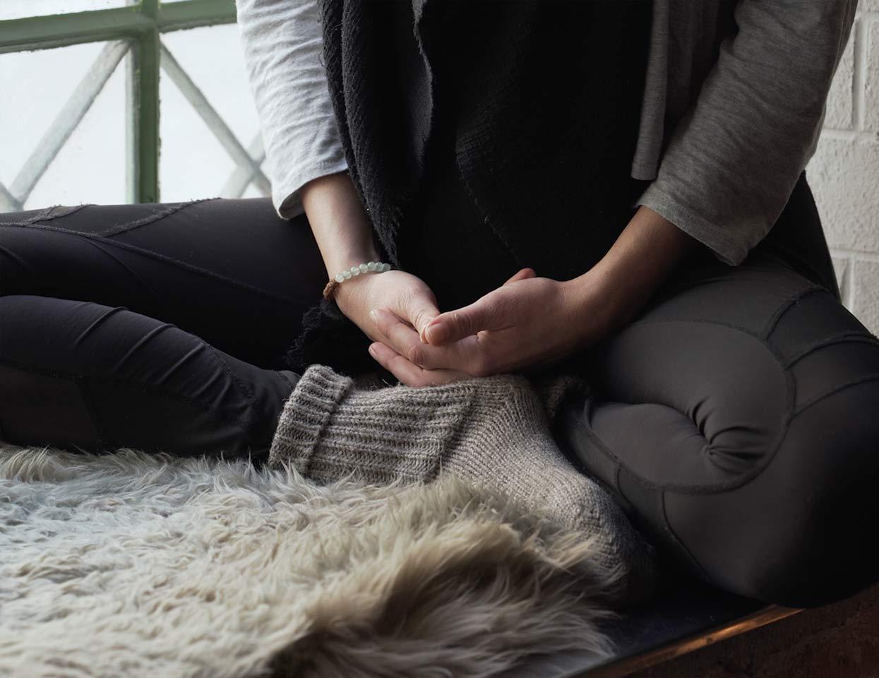 Eine Frau meditierend im Schneidersitz.